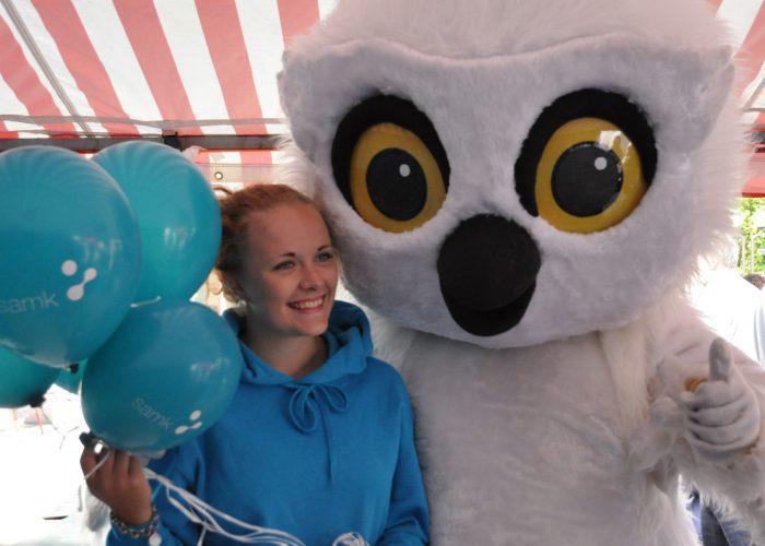 Maikkarin pöllö SAMKin teltalla ilmapallonjakajan kanssa. Kuva Marika Virtanen