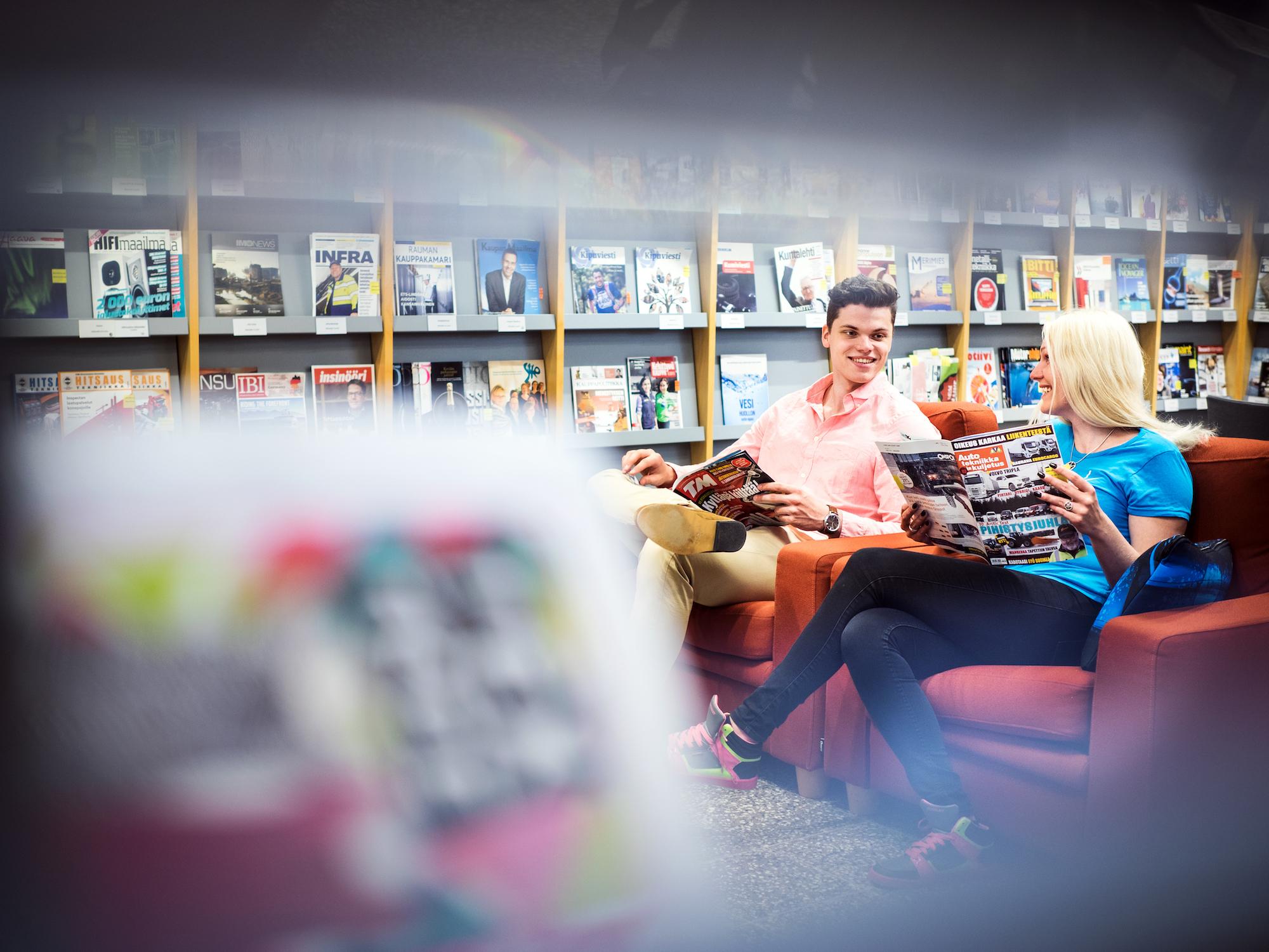 SAMKin opiskelijat Rauman kampuksen kirjastossa lukemassa lehtiä.