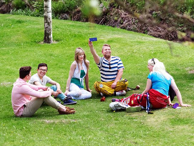 SAMKin opiskelijoita istumassa nurmikolla kesällä.