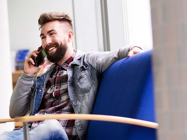 SAMKin opiskelija juttelemassa puhelimeen kampuksen käytävällä. SAMK student talking on a phone.