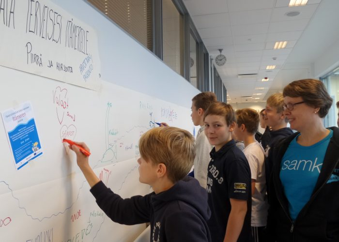 Seitsemäsluokkalaiset lähettävät taululla piirroksin terveiset Itämerelle.