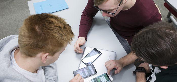 Kolme opiskelijaa tutkimassa kännyköitä.