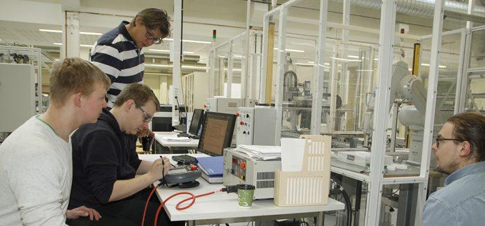 Opiskelijat Petteri Laine, Henri Hohkuri ja Juuso Kiintonen ohjelmoivat robotteja lehtori Timo Suvela opetuksessa automaatiotekniikan laboratoriossa.