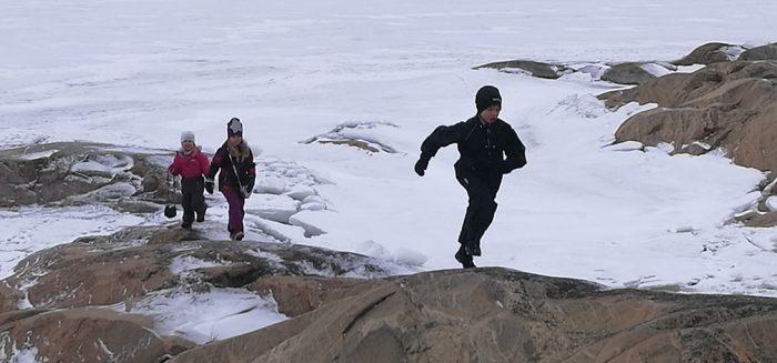 Kolme lasta juoksee rantakallioilla kylmässä kelissä.