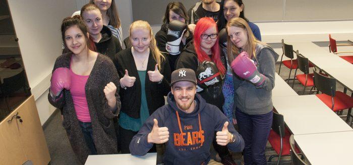 Opiskelijaryhmä poseeraa luokassa opettajan kanssa.