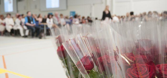 Valmistumisjuhlatilaisuus SAMKin Porin kampuksen Agora-salissa. Etualalla punaisia ruusuja ja taaempana valmistuneita ja heidän omaisiaan.