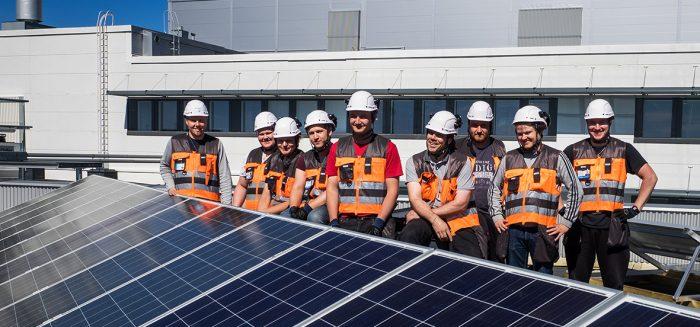 Aurinkopaneelijärjestelmä SAMKin kampuksen katolla Porissa ja sen taustalla yhdeksän henkilöä työasuissa