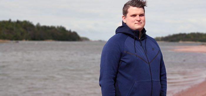 Marko Grönlund seisoo hiekkarannalla veden äärellä takki päällä.