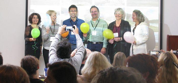 Yleisö ottaa kuvia ENPHEn hallituksen kuudesta henkilöstä, jotka seisovat luokkatilan edessä