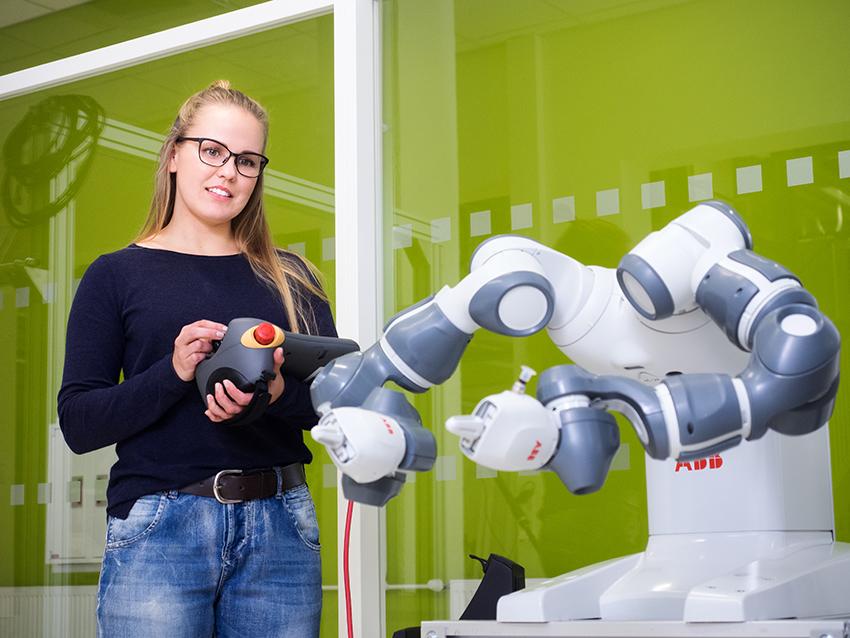 SAMKin opiskelija ohjaa robottia Porin kampuksen robotiikan laboratiossa.
