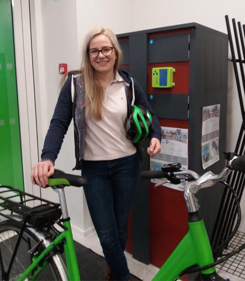 Nainen seisoo polkupyörän takana kypärä kainalossaan