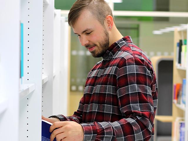 Liiketalouden opiskelija Juho Hanka SAMKin Porin kampuksen kirjastossa tutkimassa kirjoja.