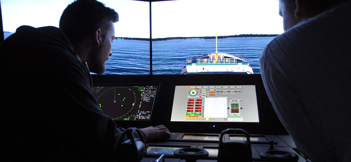 SAMK Simulator, two people drive on a simulator ship. In the front is the cockpit, in the background is the bow of the ship.