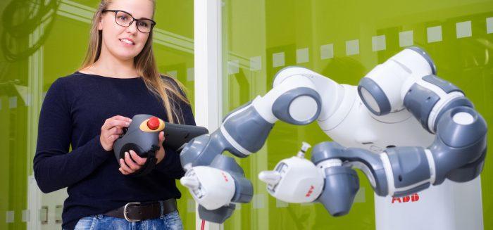 SAMKin opiskelija testaamassa robottia automaatiolaboratoriossa SAMKin kampuksella.