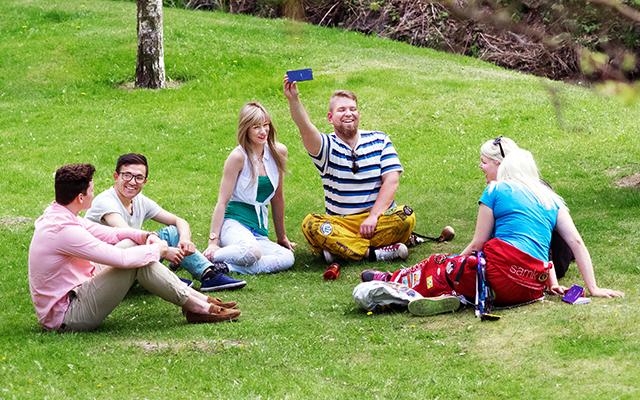 SAMKin opiskelijoita istumassa ruohikolla kesällä.