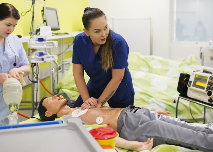 The student practices giving resuscitation with a doll