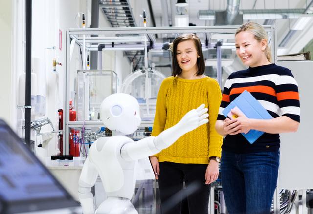 SAMKin opiskelijoita Pepperin kanssa automaatiolaboratoriossa.