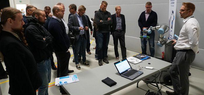 Robotiikkaseminaarin osallistujia tutustumassa yhteistyökumppanin standiin.