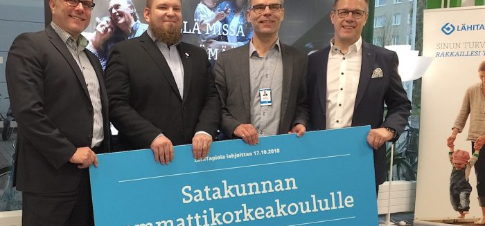 LähiTapiolan, SAMMAKKOn ja SAMKin edustajat ison lahjoituskortin takana.