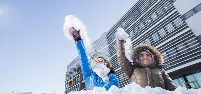 SAMKin opiskelijat heittelevät lunta Porin kampuksen edessä.