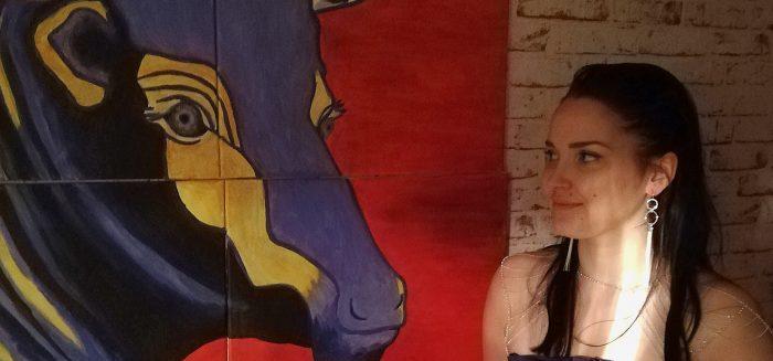 Janica Hakala lähikuvassa yhdessä lehmää kuvaavan maalauksen kanssa.