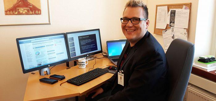 Juha Puustinen istuu työpöydän ääressä ja katsoo kameraa.