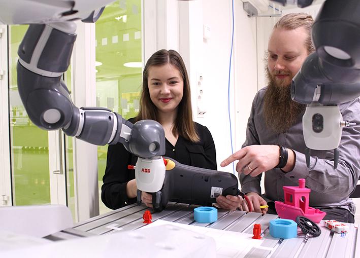 Opiskelijat testaamassa Yumi-käsivarsirobottia RoboAI:n laboratoriossa.