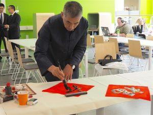 Kiinalainen professori Mr. Yu Shizhong työstämässä kalligrafiaa kankaanlle.