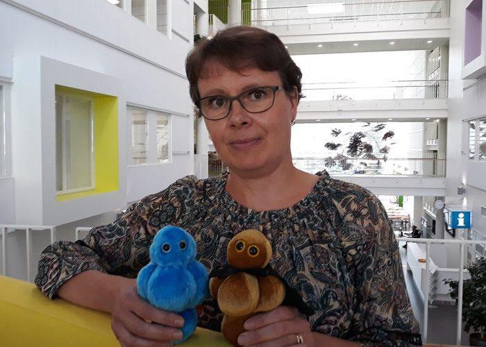 Merja Ahonen kahden pehmoelainmikrobin kanssa SAMKin Porin-kampuksen Atiumilla.