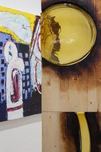 Yksityiskohta, puuta ja keltaista lasia, taustalla maalaus. More detailed view, painting in the back