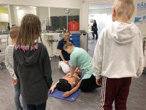 Työntekijöiden lapsia SAMK-kampus Porin simulaatioluokassa katsomassa elvytysharjoittelua Lapsi mukaan töihin -päivänä.