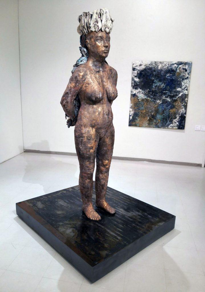 Veistos alaston nainen ja taustalla maalaus