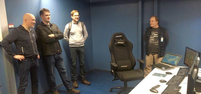 Henkilöt poseeraavat merenkulun simulaattorin ohjaushuoneessa.