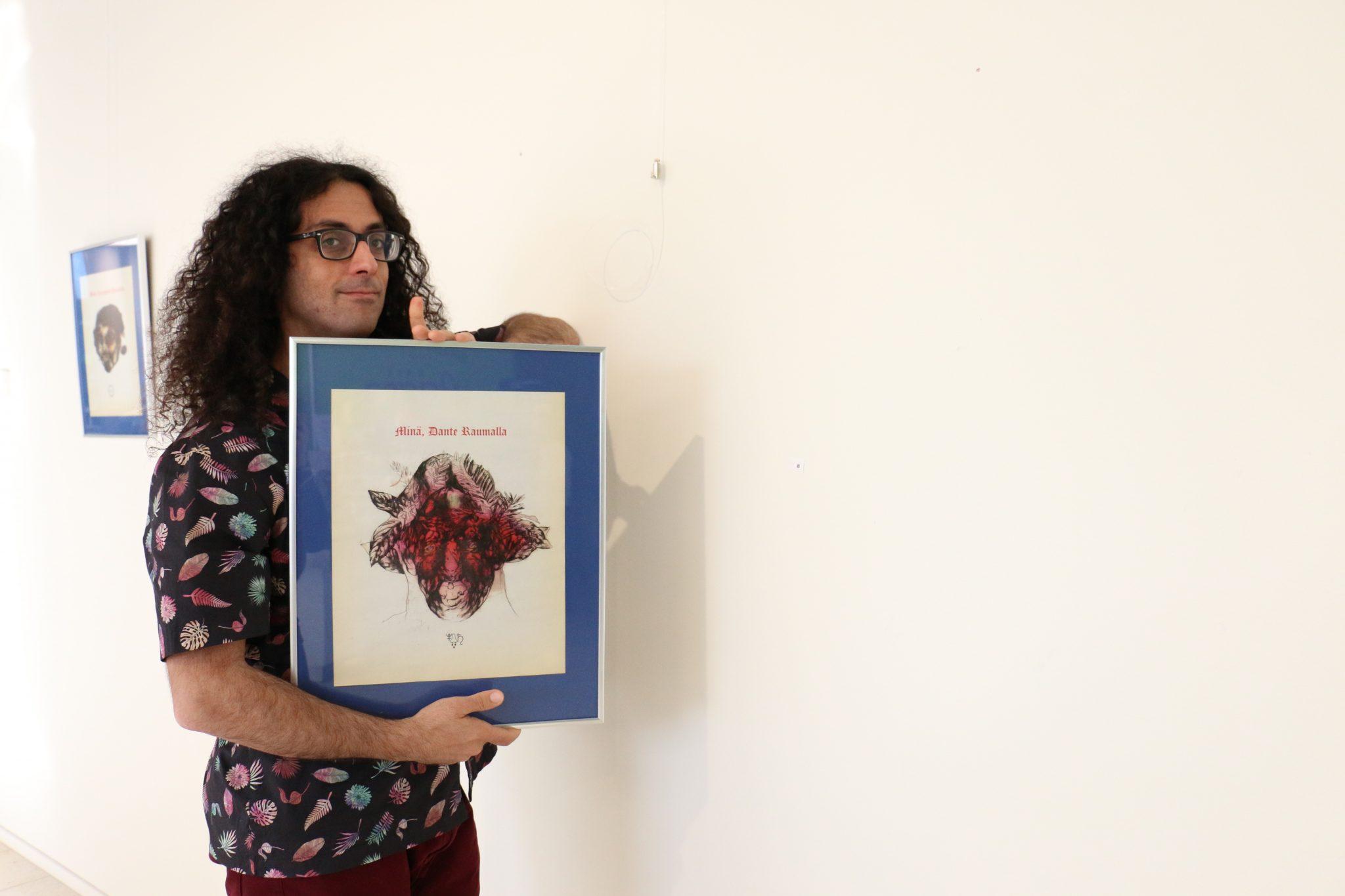 Enrico Mazzone esittelee taulua SAMKin Porin kampuksen taidekäytävällä.