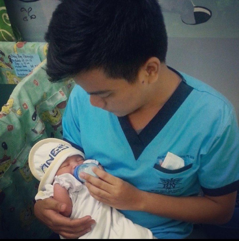 Ralph Rabang syöttää vauvaa hoitopuvussa.