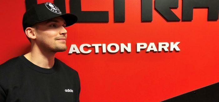 Tino Lehtonen seisoo Ultra Action Parkin logon edessä.