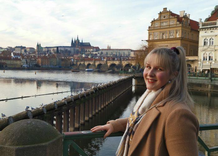 Susanna Aaltonen matkalla Vltavajoen kupeessa, jonka takana näkyy Prahan linnoitus.