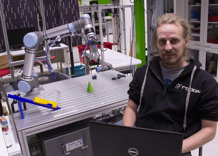 Student programming a robot at automation laboratory.