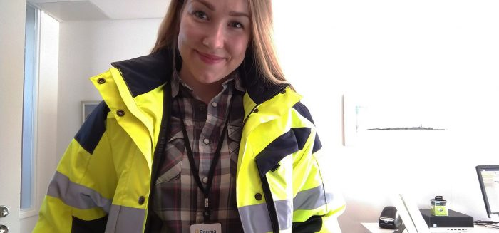 Ympäristönsuojeluinsinööri Katriina Mannonen keltaisessa huomiotakissa toimistossa