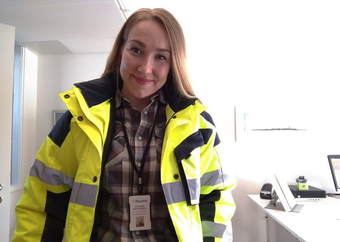 Ympäristönsuojeluinsinööri Katriina Mannonen keltaisessa huomiotakissa toimistossa. Katriina Mannonen wearing a yellow safety jacket in an office.