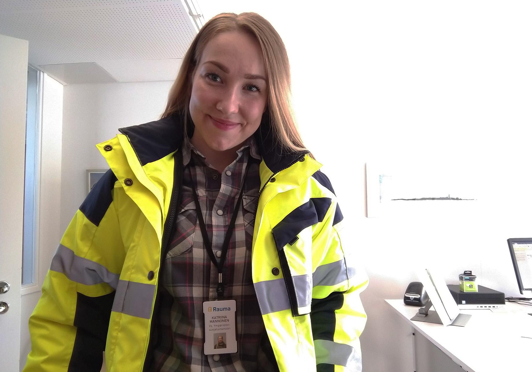 Ympäristönsuojeluinsinööri Katriina Mannonen keltaisessa huomiotakissa toimistossa. Katriina Mannonen wearing a yellow safety jacket in an office.