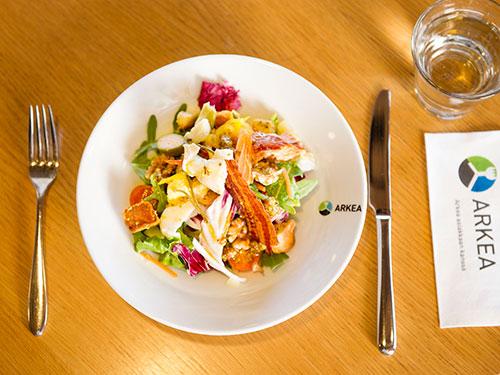 Ruoka-annos ja aterimet sekä lasi ovat pöydän päällällä.