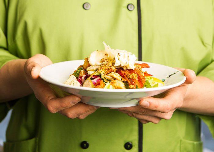 Vihreäpukuinen henkilö pitelee edessään ruokalautasta.