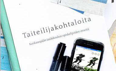 Taiteilijakohtaloita-kirja, kännykkä ja kyniä.