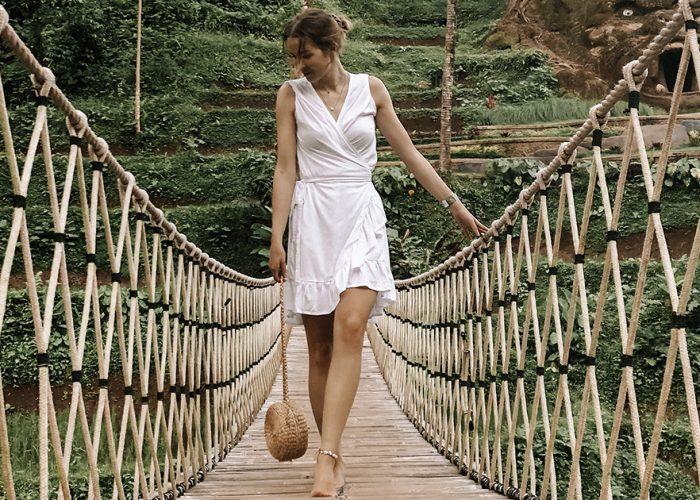 Sanna Alakulju kävelee riippusiltaa pitkin valkoisessa mekossa kassi kädessään.