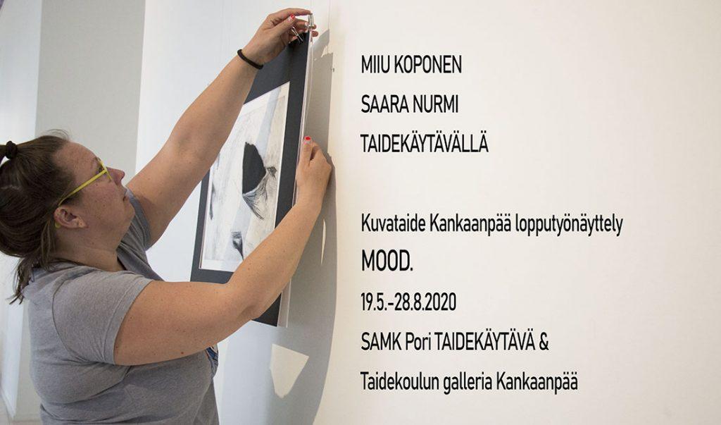 Kuvataiteilija Saara Nurmi ripustaa työtä SAMKin Taidekäytävälle.