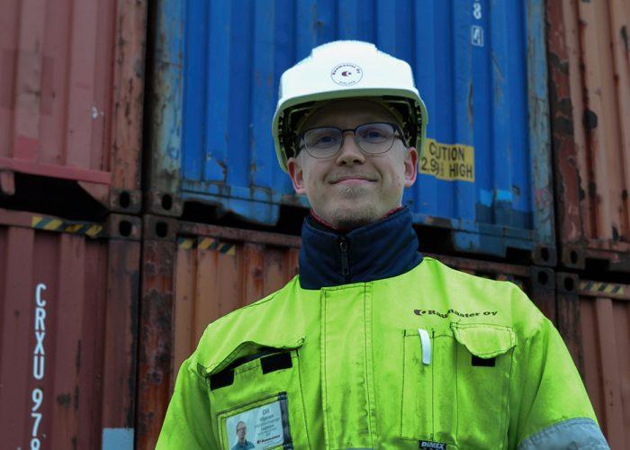 Olli Viljanen seisoo konttien edessä keltaisessa turvatakissa ja valkoisessa kypärässä.
