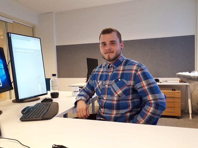 Valtteri Kaivola istuu rennosti tietokoneen ääressä työpöydän takana.