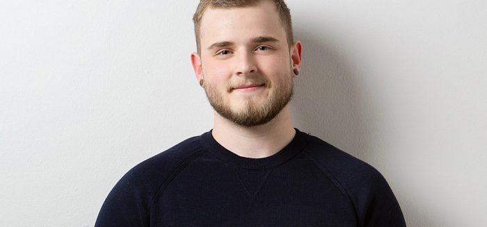 Valtteri Kaivola seisoo harmaan seinän edessä mustassa paidassa.
