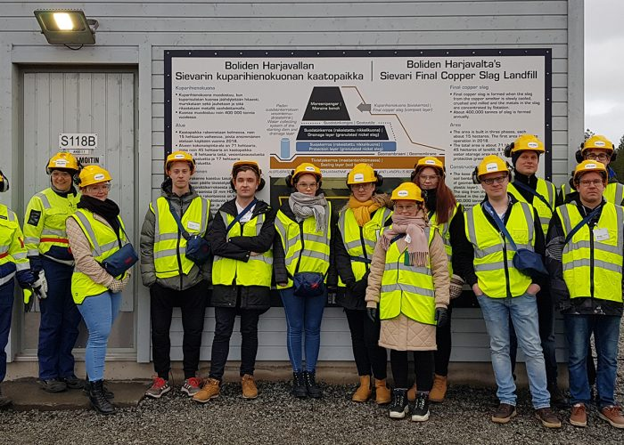 Student group wearing safety workwear and standing at copper slag landfill.